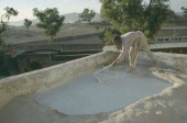 Man mending the roof of his house.