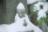 Zen Buddhist grave and statue in snow.