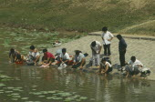 Near the China plain. People washing their clothes in the river.