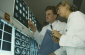 Male and female doctors examine brain scans on wall mounted light boxes