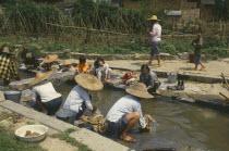 Women and children washing clothes in village stream.