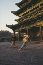 Two men doing morning exercises outside Buddhist temple
