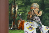 Man in costume beating gong at festival