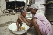Young mother washing baby in bowl in street.cleanhygiene