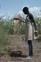 Dinka girl winnowing millet.