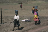 Women carrying buckets of water on their heads