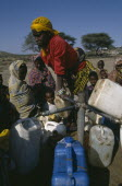Woman filling water containers at standpipe in Somali camp.