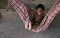 Panara indian child swinging in cloth hammock near Rio IririBrasil Kreen Akore
