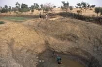 View of deep waterhole and onion fields with farmers working. Tereli
