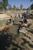 Women washing clothes in irrigation outlet