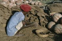 Man making dung fuel.