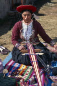 Kneeling woman in traditional costume hand weaving decorative textile.