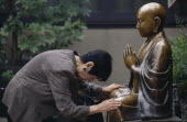 Woman praying before a seated Buddha