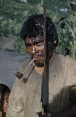 Victim after a ritual bow fight in which aim is to hit the opponent s head. Blood  now dried  has streamed from wound. Clutches his hard   macana  wood bow and quiver of arrows  smoking a clay pipeIn...