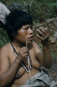 Woman applying red  ochote  facial paint extracted from ground ochote seeds  using a trade mirror and wearing traded plastic beadsIndigenous Tribes American Colombian South America Columbia Hispanic...