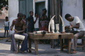 Ivory carvers working outside with watching children. Zaire