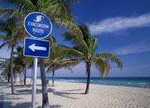 Storm Evacuation Sign on sandy beach near palm trees