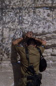 An Israeli Soldier in army uniform with a M16 Assault Riffle around his shoulder praying at The Western WallAlso known as The Wailing Wall