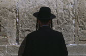 An Ultra Orthodox Jewish Man wearing a black hat and coat praying at the Western WallAlso known as The Wailing Wall
