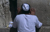 A Jewish man wearing a white Kippah praying at the Western WallAlso known as The Wailing Wall