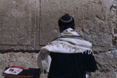 A Jewish man wearing a traditional prayer shawl praying at the Western Wall.Also known as The Wailing wall