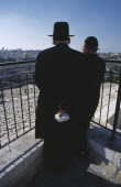 Two elderly Ultra Orthodox Jewish men one holding a bible in his hand surveying the cemetery on the Mount of Olives with the Old City in the background