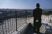 Elderly Ultra Orthodox Jewish man holding a bible in his hand surveying the cemetery on the Mount of Olives with the Old City in the background
