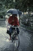 Cyclist riding through flooded street holding umbrella with one handFlood