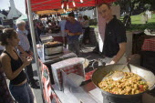 French Market. Stallholder cooking chicken and vegetable dishes in large woks with a customer waitingGreat Britain United Kingdom UK