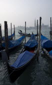 A gondolier works his gondola past others moored at the Molo San Marco with Palladios church of San Giorgio Maggiore on the island of the same name in the distance on a misty day