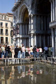Aqua Alta High Water flooding in St Marks Square with tourists queuing on elevated walkways to enter St Marks BasilicaPaul Seheult