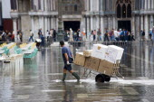 Aqua Alta High Water flooding in St Marks Square with a delivery man pulling a trolley of goods through the water with St Marks Basilica at the end of the flooded piazza