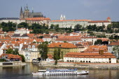 A cruise boat on the Vltava River passes the Little Quarter below St Vituss Cathedral and Prague Castle in HradcanyPraha Ceska Eastern Europe European Religion