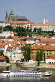 A cruise boat on the Vltava River passes the Little Quarter below St Vituss Cathedral and Prague Castle in HradcayPraha Ceska Eastern Europe European Religion