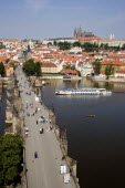 People walking on The Charles Bridge across the Vltava River leading to the Little Quarter. A river cruise boat moves up river to pass under the bridge with Prague Castle and St Vituss Cathedral on th...