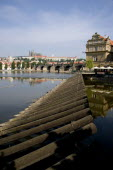 Wooden barrier at the weir on the Vltava River with the Charles Bridge and Prague Castle with St Vituss Cathedral beyond in HradcanyPraha Ceska Eastern Europe European