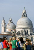 Tourists standing on the Molo San Marco with the Baroque Church of Santa Maria della Salute  by Baldassare Longhena  beyond