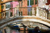A bridge over a canal with moored boats beside colourful houses on the lagoon island of Burano