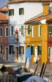 Colourful houses and a religious shrine beside a canal with moored boats on the lagoon island of Burano.