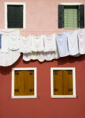 Burano Island in the lagoon. Washing hanging from a line on a colourful building between four shuttered windows