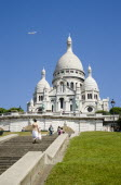 Montmartre The Facade of the church of Sacre Couer with tourists by the ballistrade at the front looking over Paris and others walking up the steps leading to the church. A plane flies in the sky abov...