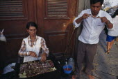 Women cooking meat skewers on barbecue with man eating nearby