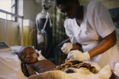 Nurse attending critically ill child in malaria research unit. African Children Eastern Africa Kenyan Kids