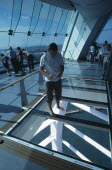 Gunwharf Quay, The Spinnaker Tower. Interior on the observation deck with a man standing on a glass floor viewing the harbour below.