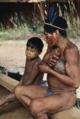 Maku hunter  face painted with red ochote marks and wearing  macaw feather crown in preparation for dance  sits beside young boy.indigenous tribe indian nomadic American Colombian Columbia Hispanic I...