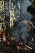 Maku hunters singeing hair from carcass of wild boar over open fire. On right of frame silhouette of anthropologist Peter Silverwood-Cope. indigenous tribe indian nomadic American Colombian Columbia...