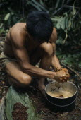 Maku nomadic hunter Umero preparing curare from root liana and bark scrapings. Once boiled to gluey consistency used as poison for blowpipe dart heads.Final process of dipping dart heads into curare t...