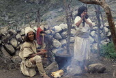 Ika brother and sister in traditional woven wool&cotton mantas cloaks  helmet of woven fique cactus fibre and wool waist belts  cook a potato and mutton sancocho - stew  outside their home using alumi...