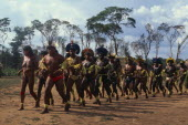 Panar� men and women performing traditional dance around central area of relocated village in Xingu National Park.  Men wearing head-dresses or crowns of feathers and face and body paint.Formally kno...