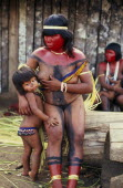 Panara woman breastfeeding daughter before dance  with face and neck painted with red karajuru and wearing multi-strand of beads across upper body and long strips of plant fibres tied around upper arm...